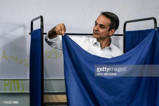 Greece's opposition party New Democracy leader Kyriakos Mitsotakis stands in a polling booth prior to casting his vote during general elections at a...