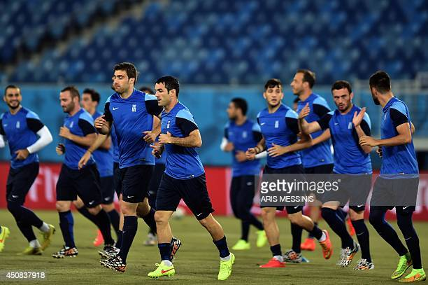 Greece's players warm up during a training session at the Dunas Arena in Natal on June 18 on the eve of their Group C football match against Japan...