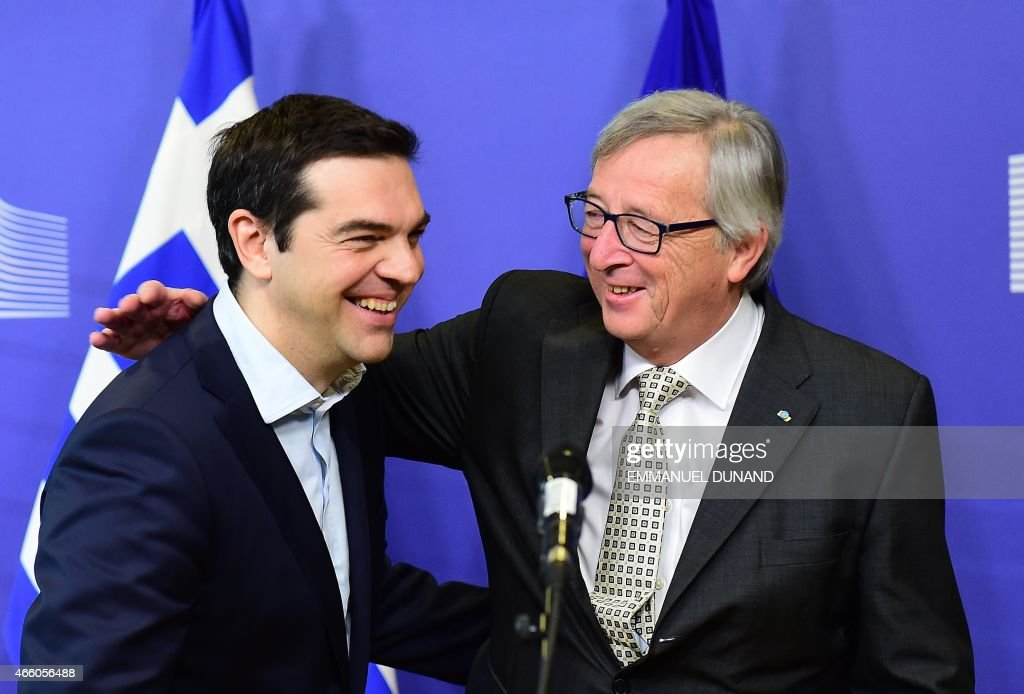 Greece's Prime Minister Alexis Tsipras (L) is welcome by European Commission President Jean-Claude Juncker at the European Commission in Brussels on March 13, 2015. Tsipras is in Brussels for talks on Athens' debt-hit bailout. AFP PHOTO / Emmanuel Dunand / AFP PHOTO / Emmanuel DUNAND