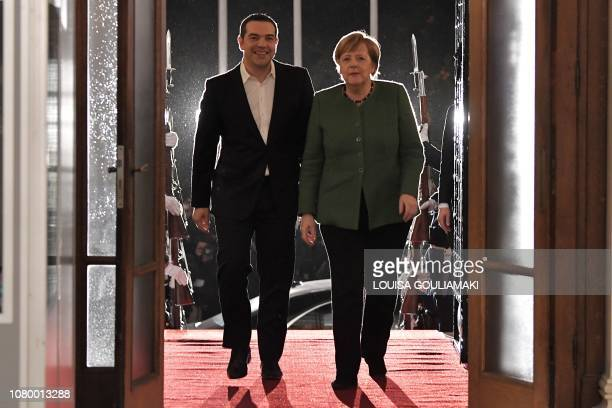 Greece's Prime Minister Alexis Tsipras walks with German Chancellor Angela Merkel during their meeting in Athens on January 10 2019 German Chancellor...