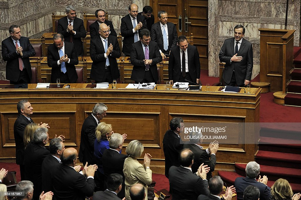 Greece's Prime Minister Antonis Samaras (Top R) is applauded by his lawmakers at the end of his speech during the parliamentary session before voting on the 2014 budget in Athens on December 7, 2013