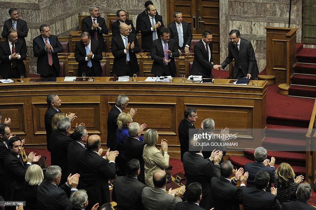 Greece's Prime Minister Antonis Samaras (Top R) is applauded by his lawmakers at the end of his speech during the parliamentary session before voting on the 2014 budget in Athens on December 7, 2013. Greece's parliament prepared to approve next year's budget, which forecasts an end to the recession that has gripped the country since 2008.