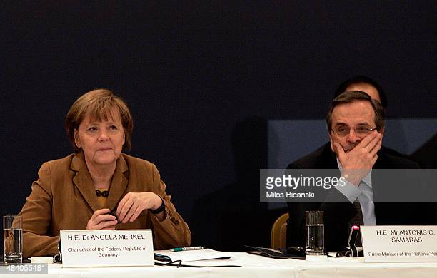 Greece's Prime Minister Antonis Samaras sits with German Chancellor Angela Merkel before a meeting with young Greek businessmen on April 11 2014 in...