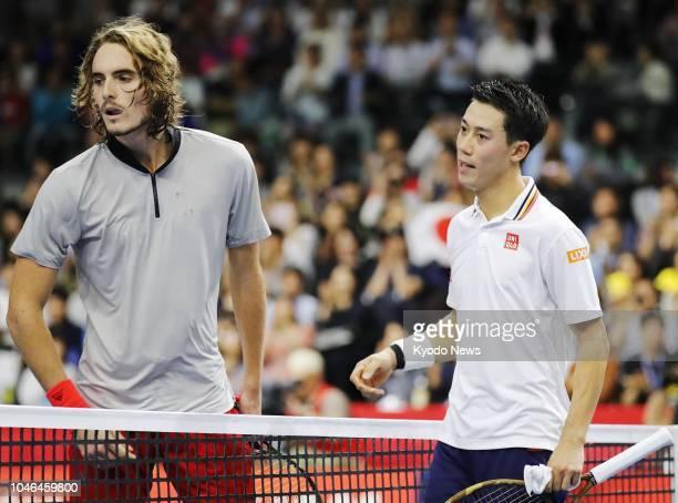 Greece's Stefanos Tsitsipas and Japan's Kei Nishikori meet at the net after completing their quarterfinal match of the Rakuten Japan Open at...