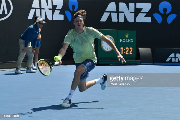 Greece's Stefanos Tsitsipas hits a return against Canada's Denis Shapovalov during their men's singles first round match on day one of the Australian...