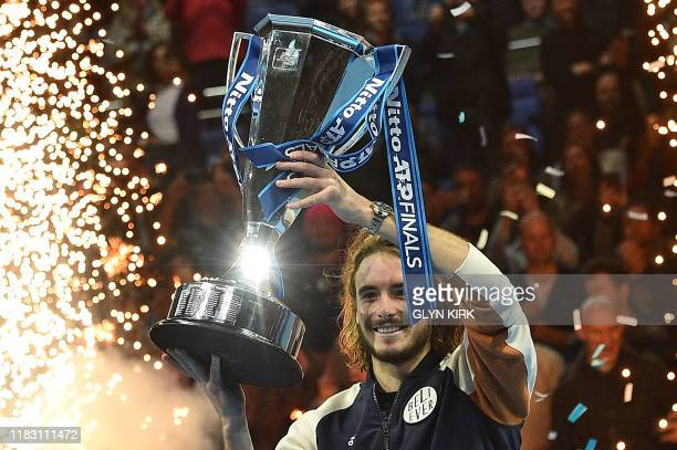 Greece's Stefanos Tsitsipas poses with the winner's trophy after winning the men's singles final match on day eight of the ATP World Tour Finals...