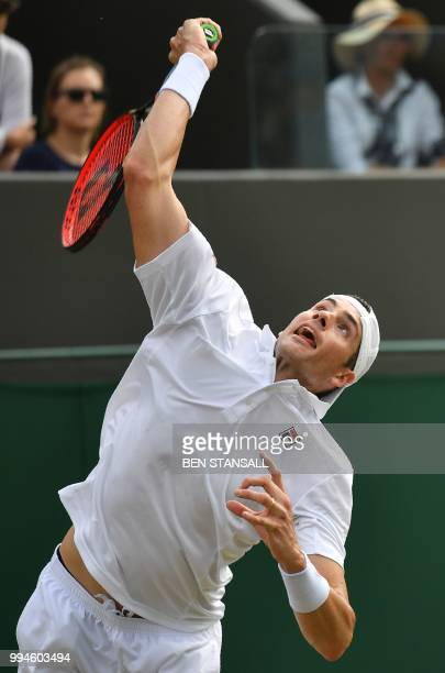Greece's Stefanos Tsitsipas serves to US player John Isner in their men's singles fourth round match on the seventh day of the 2018 Wimbledon...