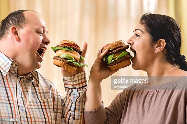 Greedy fat couple eating burgers.