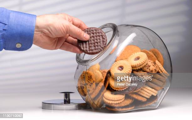 greedy man secretly reaching for chocolate biscuit - snack stock pictures, royalty-free photos & images