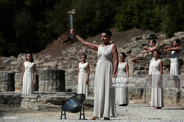 Greek actress Ino Menegaki acting as the high priestess holds the Olympic Flame at the Temple of Hera on September 29 2013 during the lighting...