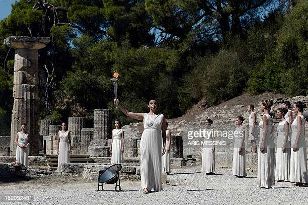 Greek actress Ino Menegaki in the role of high priestess holds the Olympic Flame on September 28 2013 in ancient Olympia the sanctuary where the...