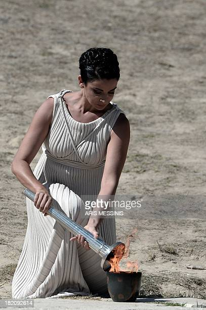 Greek actress Ino Menegaki transfers the Olympic Flame into a pot on September 28 2013 in ancient Olympia the sanctuary where the Olympic Games were...