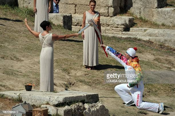 Greek actress Ino Menegakie acting as the priestesses passes the flame to the first torch bearer Greek skier Giannis Anoniou at the Temple of Hera on...