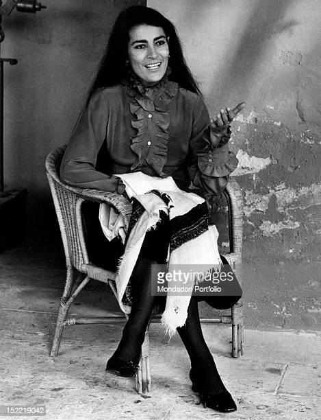 Greek actress Irene Papas chattering on a wicker chair Venice 1970