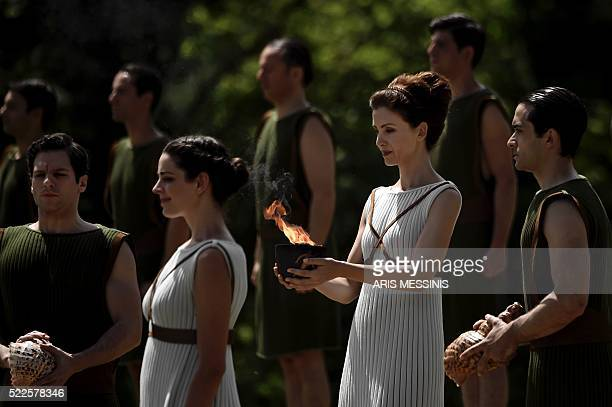 Greek actress Katerina Lechou acting as the high priestess holds a cauldron with the Olympic flame at the ancient stadium of Olympia on April 20...