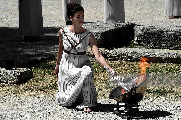Greek actress Katerina Lechou acting as the high priestess lights the Olympic flame at the Temple of Hera in Olympia on April 20 during a dress...