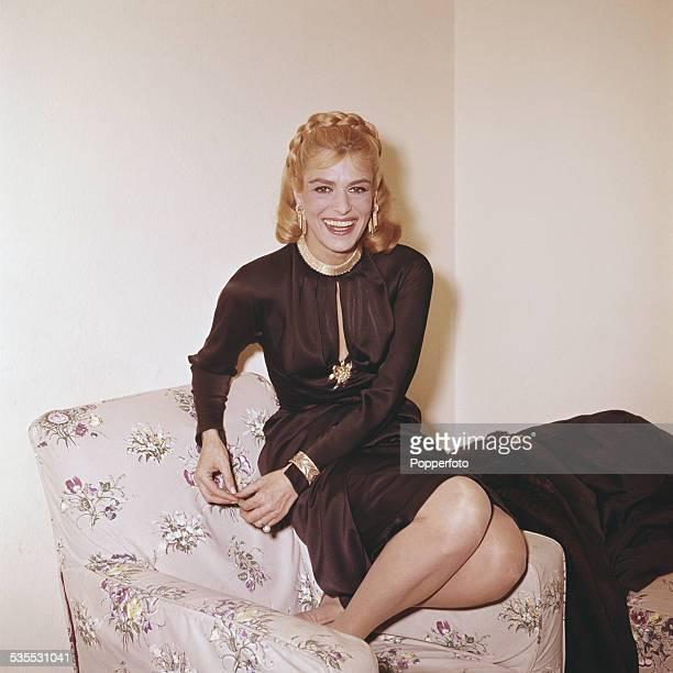 Greek actress Melina Mercouri pictured seated on a chair wearing a black evening dress with gold jewellery in London in 1962
