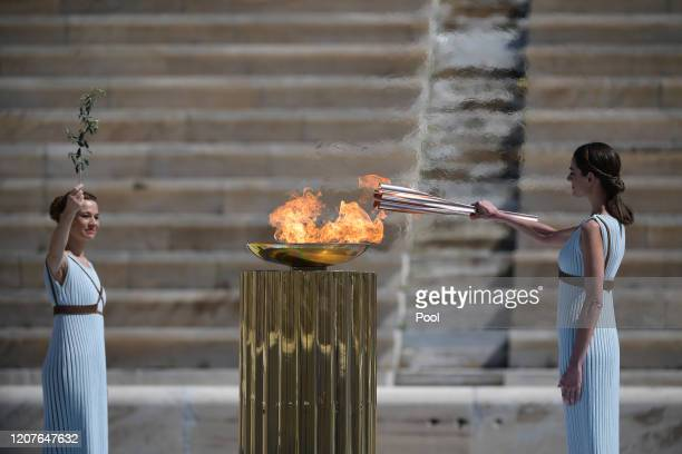 Greek actress Xanthi Georgiou dressed as an ancient Greek high priestess lights the olympic torch during the Flame Handover Ceremony for the Tokyo...