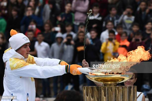 Greek Alpine skier Ioannis Proios lights an Olympic torch from a cauldron at The Panathenaic Stadium in Athens on October 31 during the handover...