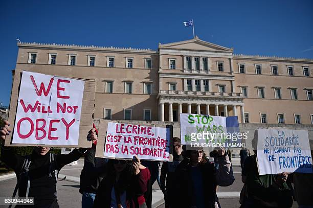 """Greek and foreign pro-migrant activists hold placards reading """"Crime is the border not solidarity"""" and """"Solidarity knows no borders"""" as they..."""