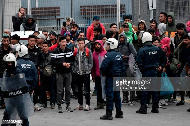 Greek antiriot police gathers migrants and refugees from the Moria camp who stayed outside the port of Mytilene on the island of Lesbos hoping to get...