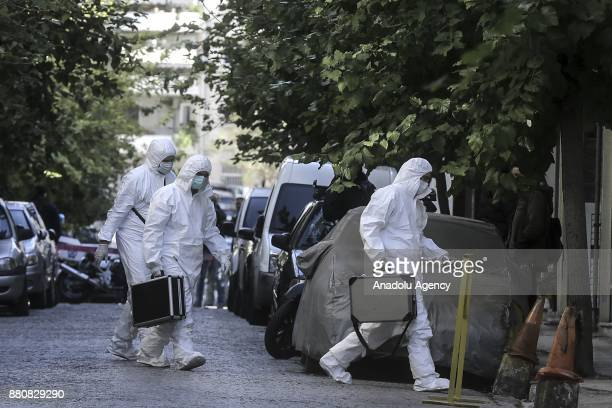 Greek antiterrorist police inspect the site after they raided three houses in the Kallithea and Neos Kosmos districts and found explosives and wires...