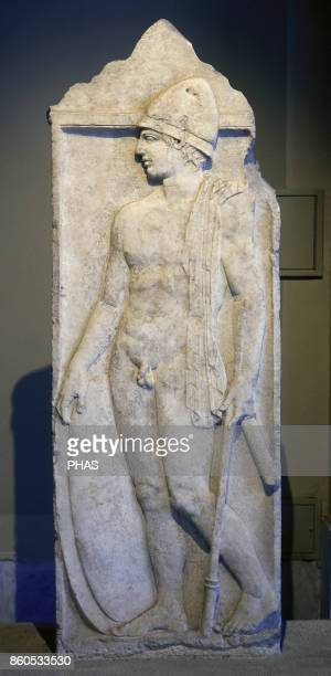 Greek archaic style Funerary stele of a warrior of Pella Dated around 350 BC Relief depicting a young Greek warrior with helmet carrying his weapon...