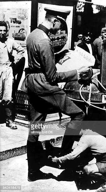 Greek boy is shining the shoes of a German soldier who is reading a newspaper