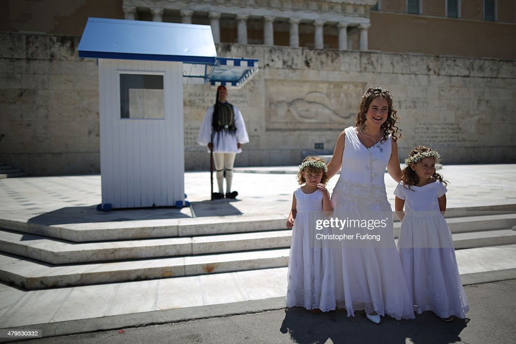 Greek bride Irene poses for pre-wedding photographs with her bridesmaids outside the Greek Parliament building. Irene declared to tourists as she gave a victory sign ' The only time I will say Yes today is to my new husband' on July 5, 2015 in Athens, Greece. The people of Greece are going to the polls to decide if the country should accept the terms and conditions of a bailout with its creditors. Greek Prime Minister Alexis Tsipras is urging people to vote 'a proud no' to European creditors' proposals, and 'live with dignity in Europe'. 'Yes' campaigners believe that a no vote would mean financial ruin for Greece and the loss of the Euro currency.