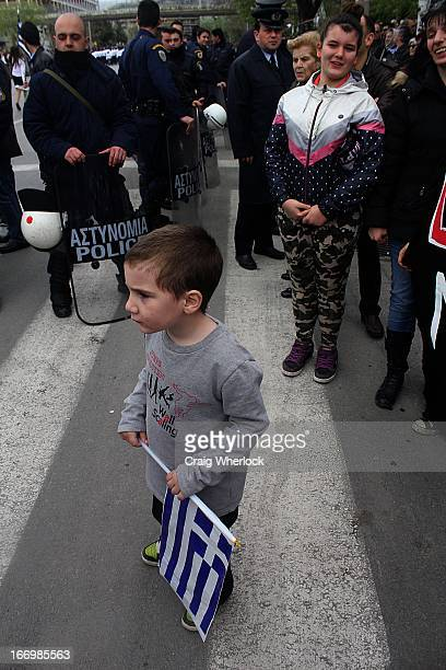 CONTENT] Greek child holding national flag stands in front of riot police unit during independence day parade Thessaloniki Greece