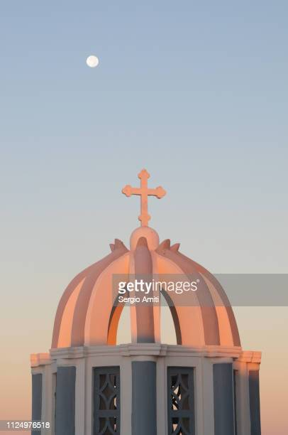 Greek church dome and cross spotlit at sunrise