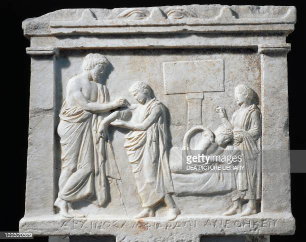 Greek civilization 5th4th century bC Votive marble relief depicting Amphiaraus healing Archinus' shoulder From the Temple of Amphiaraos at Oropos...