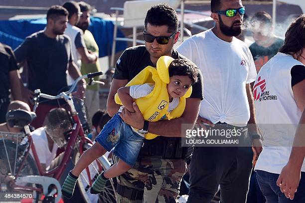 A Greek coast guard carries a migrant child at the port of Kos after intercepting a group of migrants at sea between Greece and Turkey off Kos island...