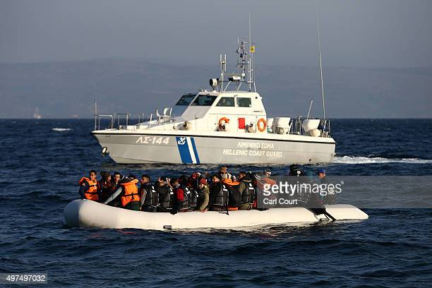 Greek coastguard vessel watches a migrant boat as it makes the crossing from Turkey to the Greek island of Lesbos on November 17 2015 in Sikaminias...