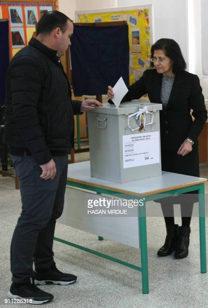 A Greek Cypriot woman casts her vote at a polling station in the capital Nicosia in the first round of the east Mediterranean island's presidential...