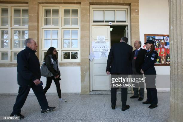 Greek Cypriots arrive to cast their vote at a polling station in the capital Nicosia in the first round of the east Mediterranean island's...