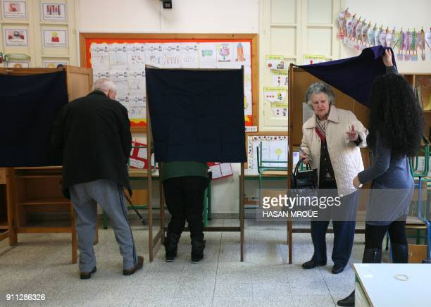 Greek Cypriots cast their vote at a polling station in the capital Nicosia in the first round of the east Mediterranean island's presidential...