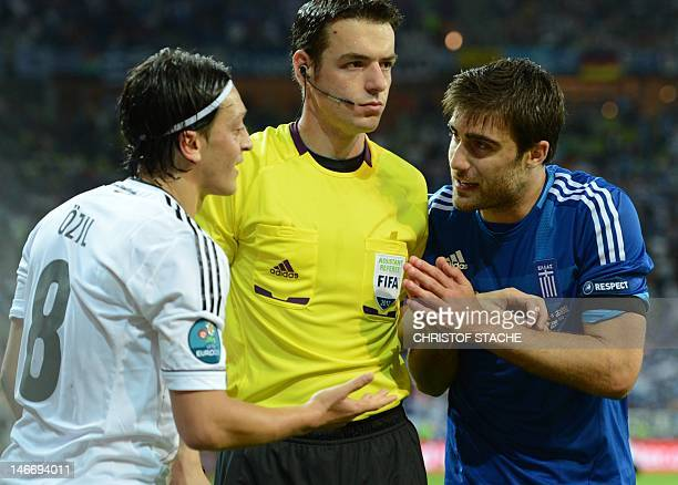 Greek defender Sokratis Papastathopoulos argues with German midfielder Mesut Oezil during the Euro 2012 football championships quarterfinal match...