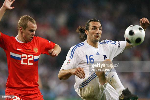 Greek defender Sotirios Kyrgiakis vies with Russian defender Alexander Anyukov during the Euro 2008 Championships group D football match Greece vs...