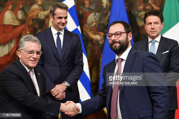 Greek Deputy Minister for Energy and Natural Resources, Gerassimos Thomas shakes hand with Italy's Minister of Economic Development Stefano...