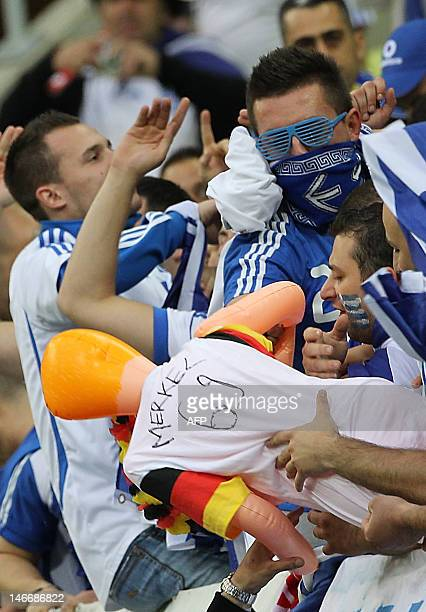 Greek fans play with a blow up doll with a German jersey with the name of German chancelor Angela Merkel prior to the Euro 2012 football...
