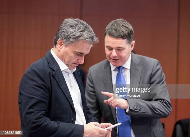 Greek Finance Minister Euclid Tsakalotos is looking at his smartphone with the Irish Minister for Public Expenditure and Reform Paschal Luke Donohoe...