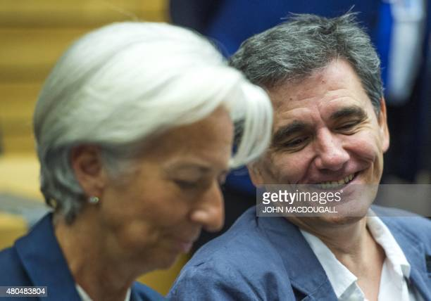 Greek Finance Minister Euclid Tsakalotos smiles as he speaks with Managing Director of the International Monetary Fund Christine Lagarde during a...