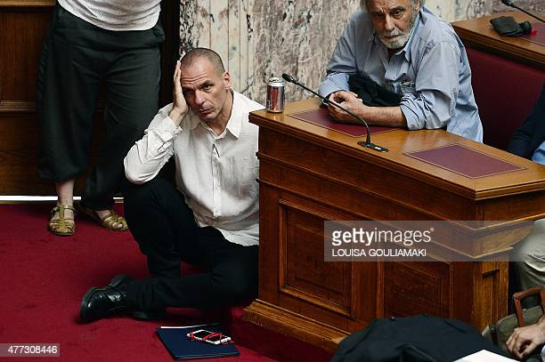 Greek Finance Minister Yianis Varoufakis listens to Prime Minister addressing his MP's and ministers, next to Syriza lawmaker Konstantinos Tsoukalas...
