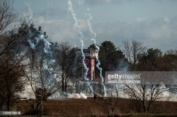 Greek firefighter stands amid clouds of tear gas at the Greece-Turkey border during clashes between migrants and riot police in the village of...