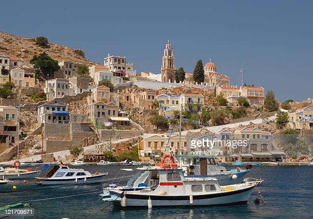 greek fishing boats in protected harbor - symi stock photos and pictures