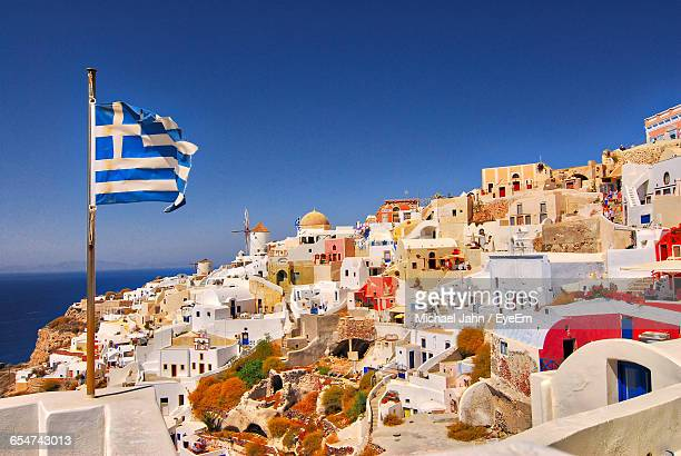greek flag against townscape - greek flag stock pictures, royalty-free photos & images
