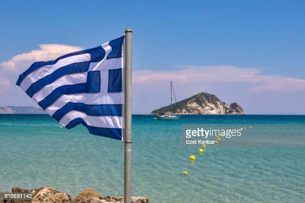 Greek flag , emerald sea and Marathonisi island , Zakynthos island, Ionian Islands Greece