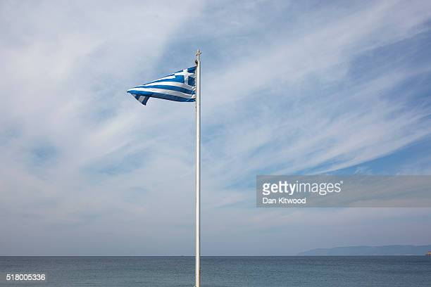Greek flag flies next to the shoreline on March 29 2016 in Petra Lesbos Greece New boat arrivals of refugees and migrants on the island of Lesbos...