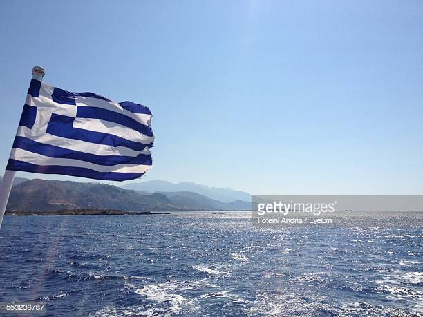 Greek Flag Over Sea Against Clear Sky